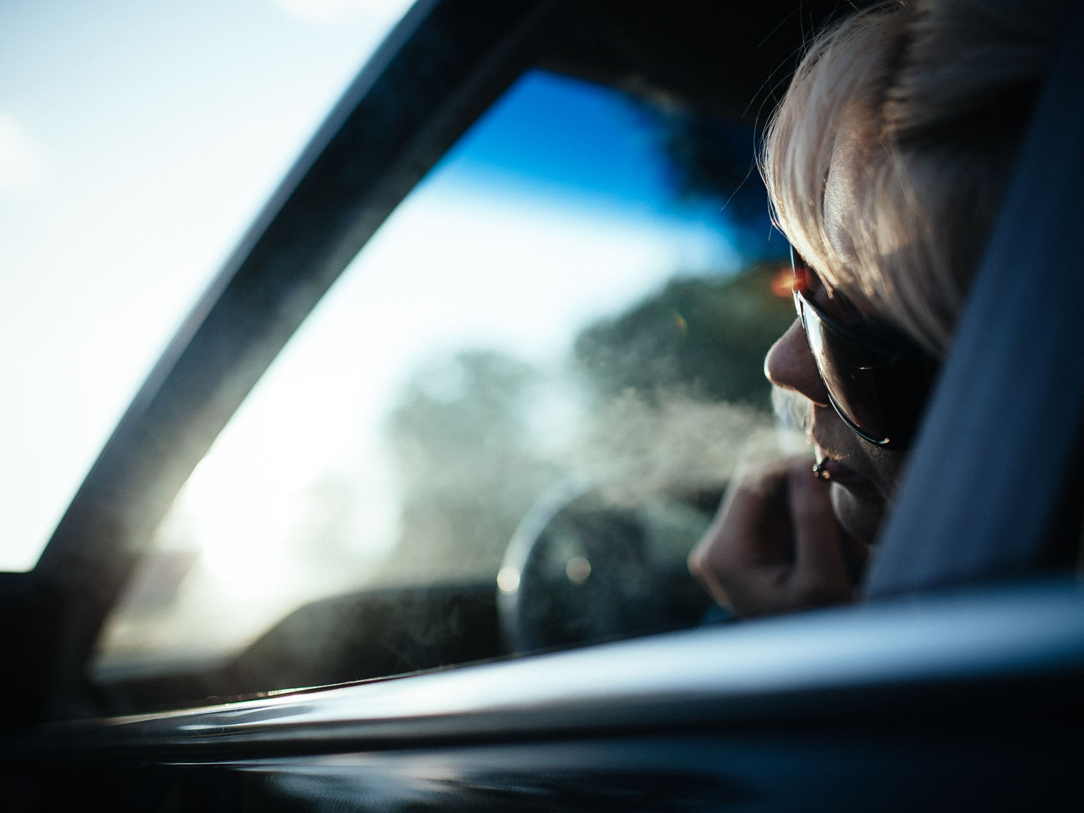 Girl smoking out of her car