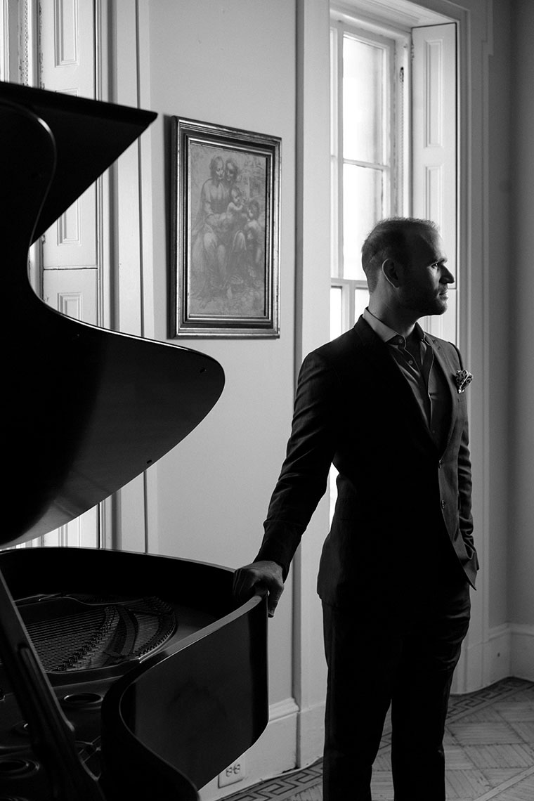 Opera singer standing by the piano black and white portrait.
