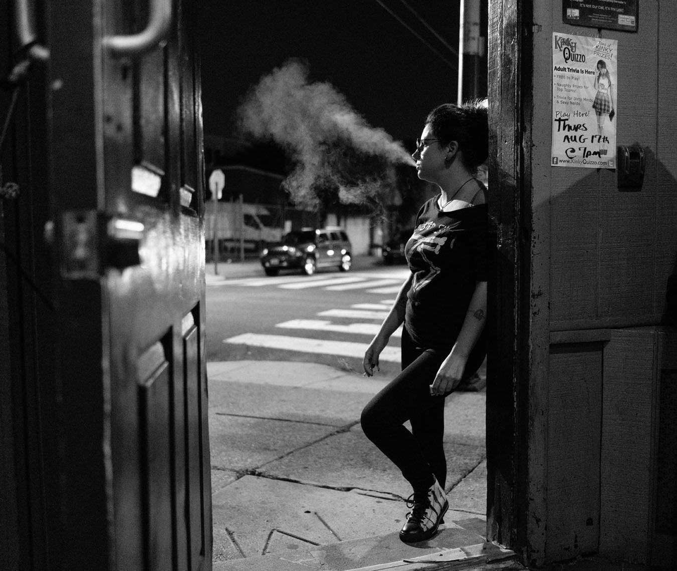 Philadelphia dive bar with young female silhouette smoking in the door frame